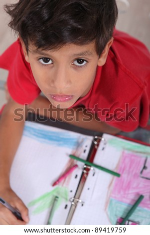 Top-view of bored little boy at school - stock photo