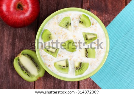 Top view of bowl with oatmeal and yogurt with sliced kiwi. Fruits and oatmeal on the table. Apple, oatmeal, kiwi. Vegetarian breakfast. Round green bowl of oatmeal. - stock photo