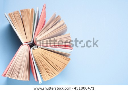 Top view of bright colorful hardback books in a circle. Open book, fanned pages.   Education essential for self improvement, gaining knowledge and success in our careers, business and personal lives. - stock photo