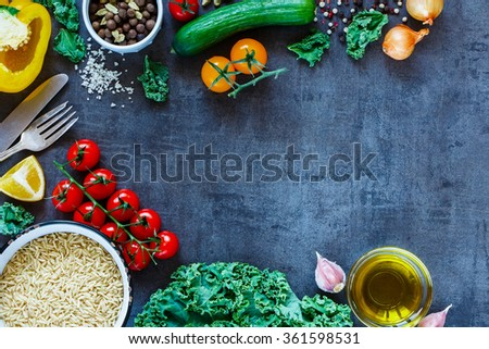 Top view of brown rice with fresh delicious vegetables and ingredients for tasty cooking on vintage dark background. Diet or Sports nutrition concept. - stock photo