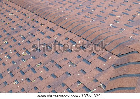 Top view of brown roof shingles with a few autumn leaves on the surface. Selective focus with a blurred background. - stock photo
