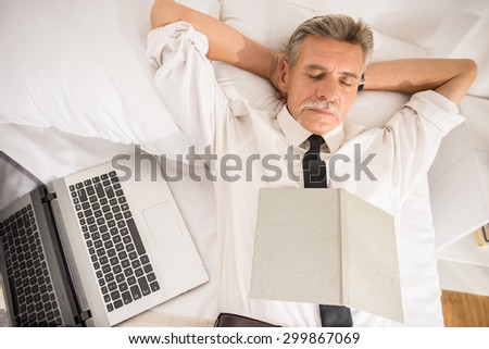 Top view of business man is sleeping in suit with notebook and laptop on bed at the hotel room. - stock photo