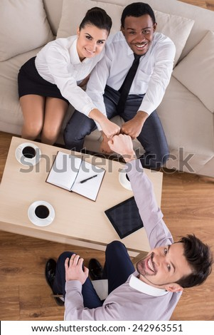 Top view of business people are shaking hands while working in cosy meeting room. - stock photo