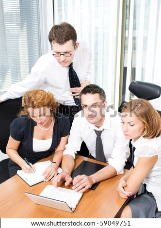 Top view of business people sitting round table in board room and discussing business projects. The main manager showing the information on the laptop computer.