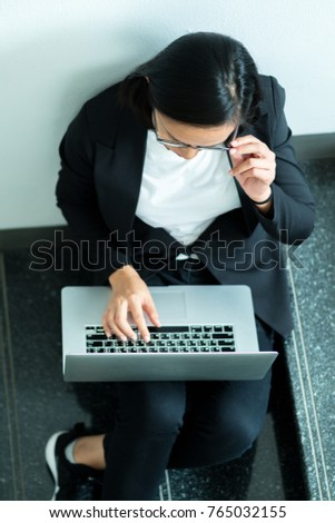 Top view of business woman sitting usining laptop at the stairs and hand touching glasses.
