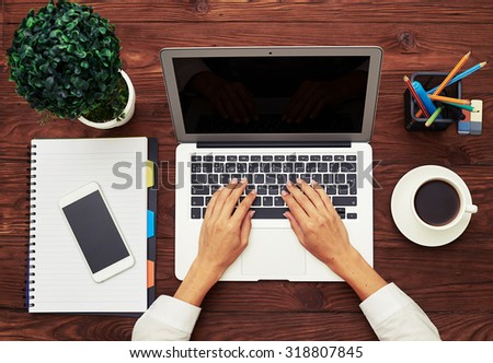 top view of business workspace with laptop, notebook, cup of coffee and female hands typing on keyboard - stock photo
