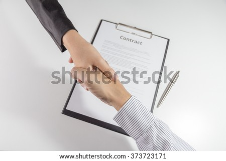 Top view of businessman and businesswoman handshake over the  contact document. - stock photo