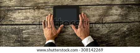 Top view of businessman hands holding black digital tablet on textured antique wooden desk. - stock photo