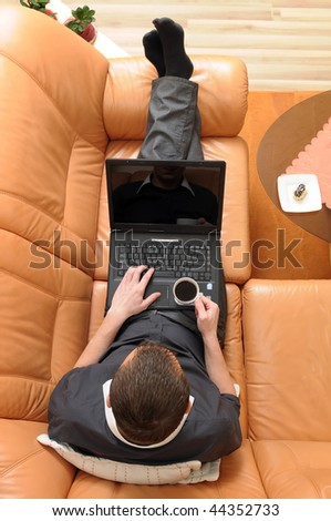 Top view of businessman holding a cup of coffee and working on portable computer on luxurious sofa. - stock photo
