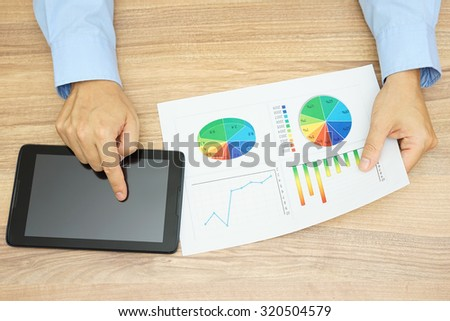 top view of businessman  is analyzing financial report and using tablet computer at the same time, - stock photo