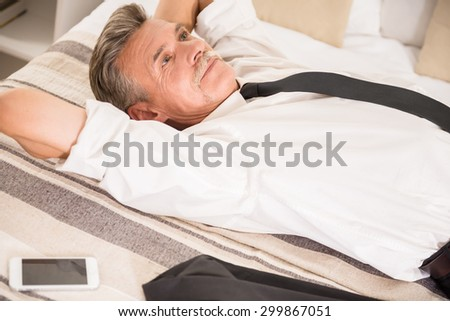 Top view of businessman is lying with his phone on bed and dreaming about something. - stock photo