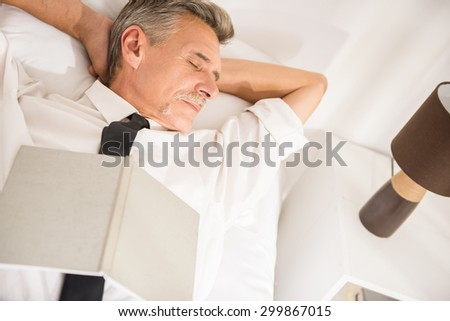 Top view of businessman is sleeping in suit with notebook on bed at the hotel room. - stock photo