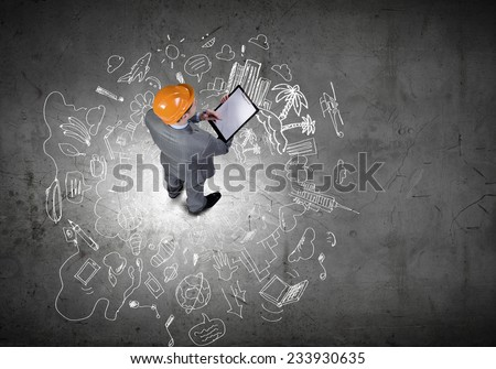 Top view of businessman looking at business sketches on floor - stock photo