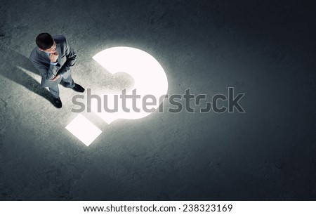 Top view of businessman looking at question mark on floor - stock photo