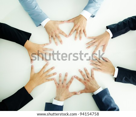 Top view of businesspeople holding hands together on a plain white surface - stock photo