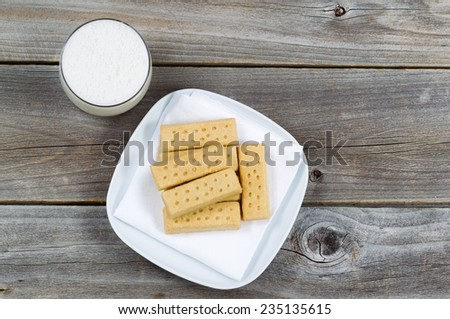 Top view of butter cookies on white cloth napkin and a glass of rich milk with rustic wood underneath - stock photo