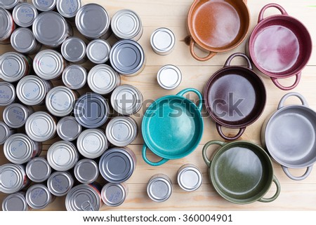 Top view of canned food and ceramic soup bowls - stock photo