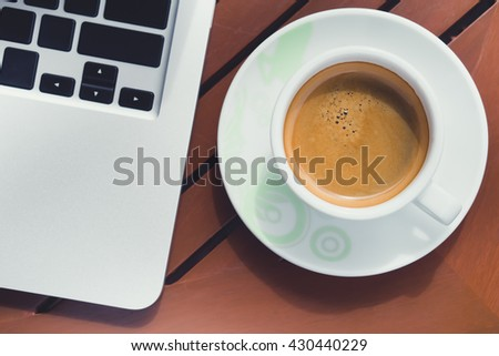 Top view of Capuchino coffee in a white cup on black background and laptop.
