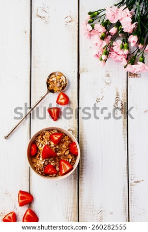 Top view of cereal and strawberry on white wooden background. Healthy breakfast. - stock photo