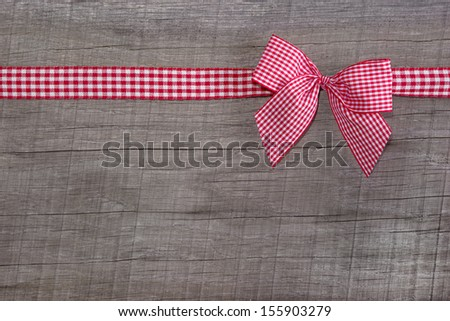 Top view of checked ribbon decoration on wooden background for christmas or for a voucher for birthday like a present - stock photo