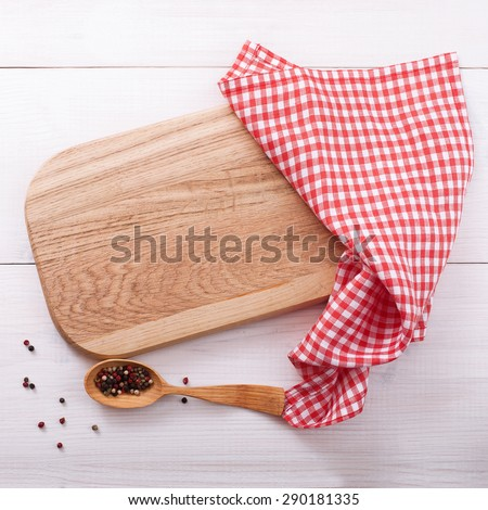 Top view of checkered napkin tablecloth on white wooden table. Empty cutting board. Unique perspectives horizontal - stock photo