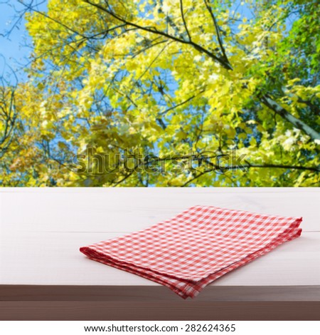 Top view of checkered napkin tablecloth on white wooden table. Flat mock up for design. Summer blurred background. - stock photo