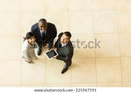 top view of cheerful business team using tablet computer - stock photo