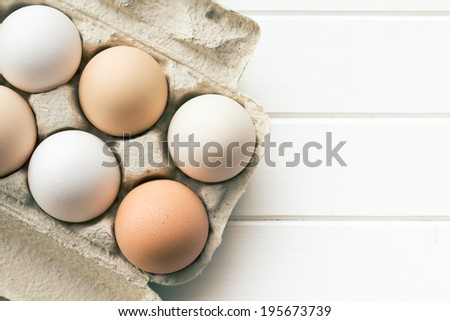 top view of chicken eggs in egg box - stock photo