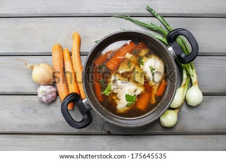 Top view of chicken soup on wooden table - stock photo