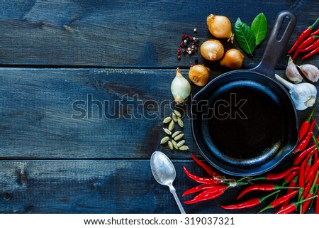 Top view of chili hot red peppers, garlic, onion with spices and herbs for use as cooking ingredients on dark wooden background with space for text. Vegetarian food, health or cooking concept. - stock photo