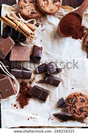 Top view of chocolate and cookies  composed on paper, selective focus - stock photo