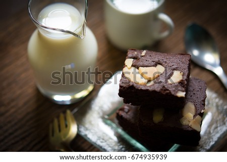 Top view of chocolate brownies Serve with milk and glass of water on the dark wood table. Vintage style.