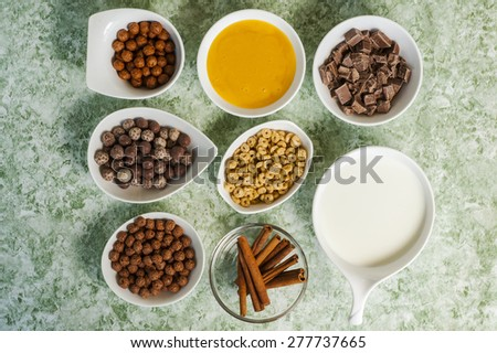 top view of chocolate cereals in bowl and milk in jar and cinnamon and honey