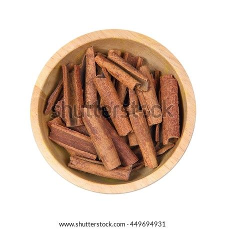 Top view of Cinnamon sticks in wooden bowl on white background.