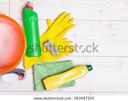 Top view of cleaning supplies and tools for house keeping on the bright laminate floor - stock photo