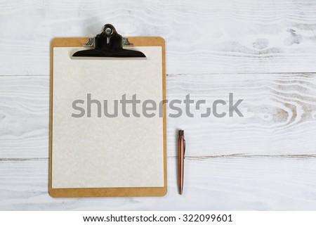 Top view of clipboard with antique pen, paper on white desktop.  - stock photo