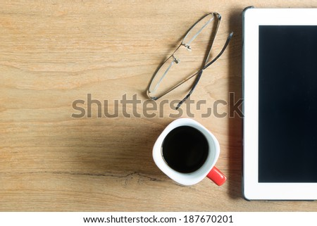 Top view of coffee cup , glasses and tablet on wooden table with space - stock photo