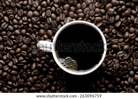 Top view of coffee cup on coffee beans - stock photo