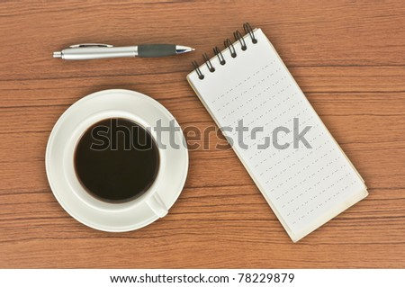 Top view of coffee cup, spiral notebook and pen on the wooden table