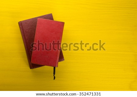 Top view of colorful hardback books on yellow background. Composition with vintage old hardback books, diary, fanned pages on wooden deck table. Books stacking. Back to school. Copy Space. - stock photo