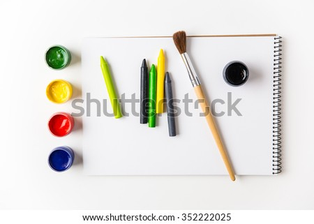Top view of colorful paints, crayons and brushes lying on art album  - stock photo