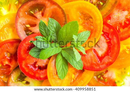 top view of colorful tomato slices with green twig mint, fresh organic food - stock photo
