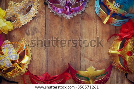top view of colorful Venetian masquerade masks on wooden table. retro filtered image  - stock photo