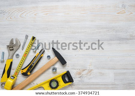 Top view of construction instruments and tools on wooden DIY workbench. with open space. Level, tape measure, wrench, hammer, cutter. - stock photo