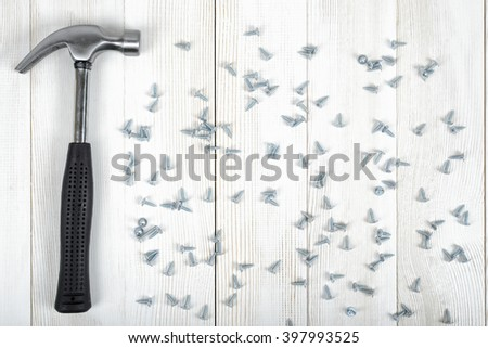 Top view of construction tools including hammer and screws distributed over the entire wooden workbench surface - stock photo