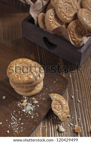 Top view of cookies in the box on wooden board. Biscuits stack and one broken cookie with crumbs on cutting board. - stock photo
