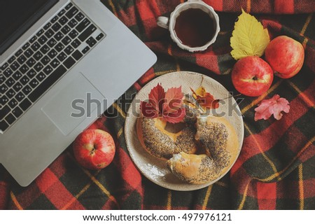 Top view of cozy autumn morning at home. Breakfast with laptop, cup of tea and bagel with apples on woolen plaid blanket. Working at home.