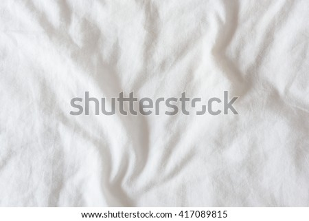 Top view of creased / wrinkles on a white unmade / messy bed sheet after waking up in the morning. Bedsheet is not neatly arranged for new guests or customers to sleep in. Abstract texture background - stock photo