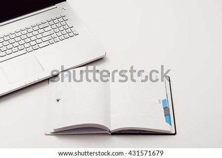 Top view of creative drawing or writing theme concept. Notepad or vintage calendar and crumpled paper on white, wooden table background.