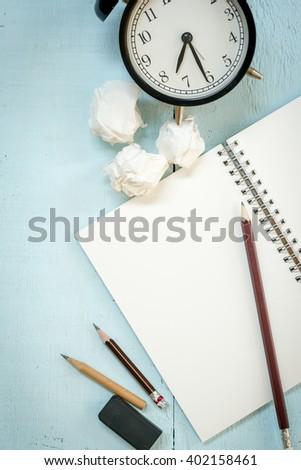 Top View of Creative Writing Concept With Pencils, Book, Notepad, Crumpled paper and Alarm Clock on Wooden Table - stock photo